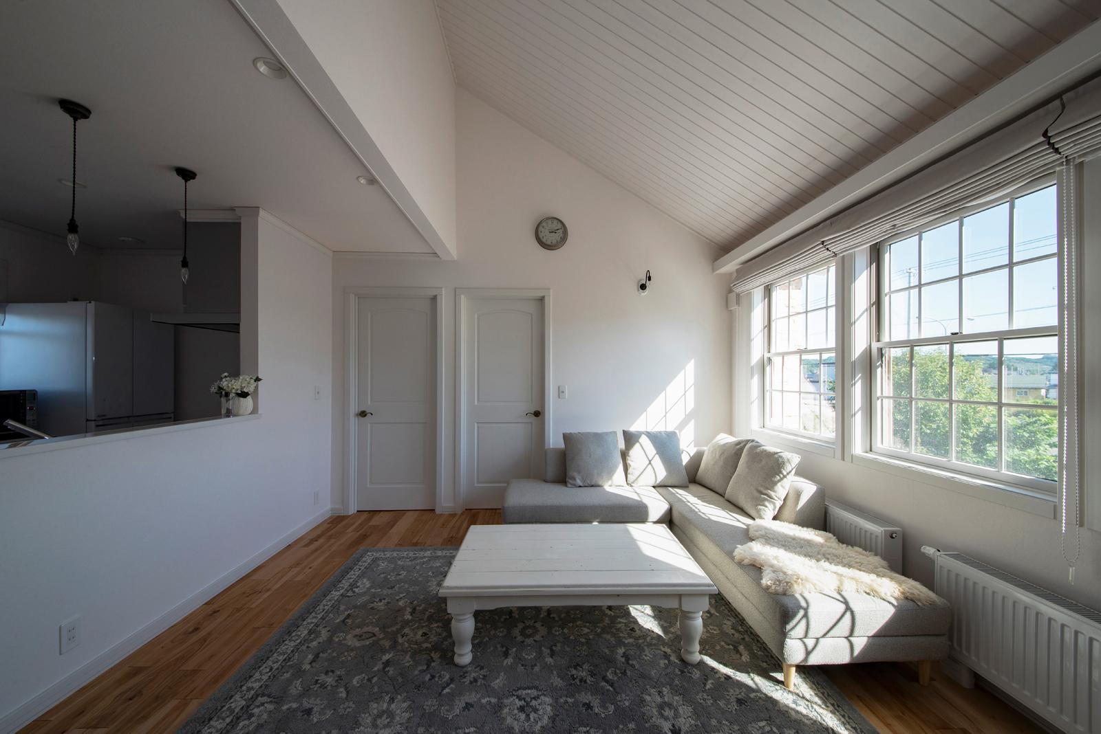3連窓と屋根なり天井を採用したリビング。子世帯の生活空間は、白を基調に、カバ無垢幅広フローリング材を採用し、若々しいイメージで仕上げた