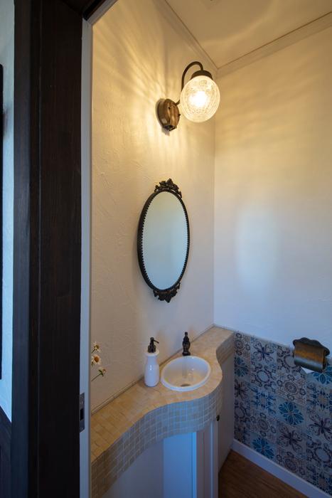 スペイン風タイルと塗り壁が異国情緒を漂わせるカフェのトイレは、お客さんに大好評。モザイクタイルを用いた手洗いも造作仕様