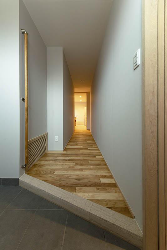 玄関からまっすぐ伸びる廊下は肌触りのよいナラの無垢フローリング