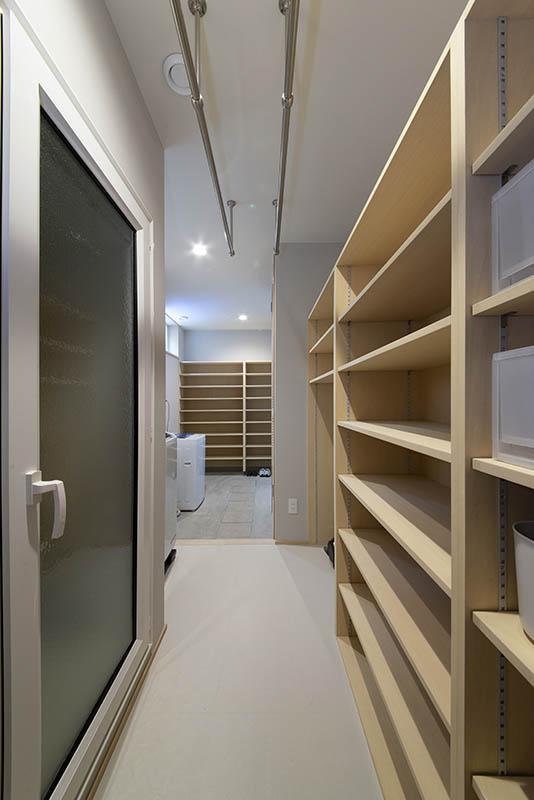 玄関と廊下の裏側には広い土間とシューズクローゼット。洗濯機と収納棚をひとまとめに