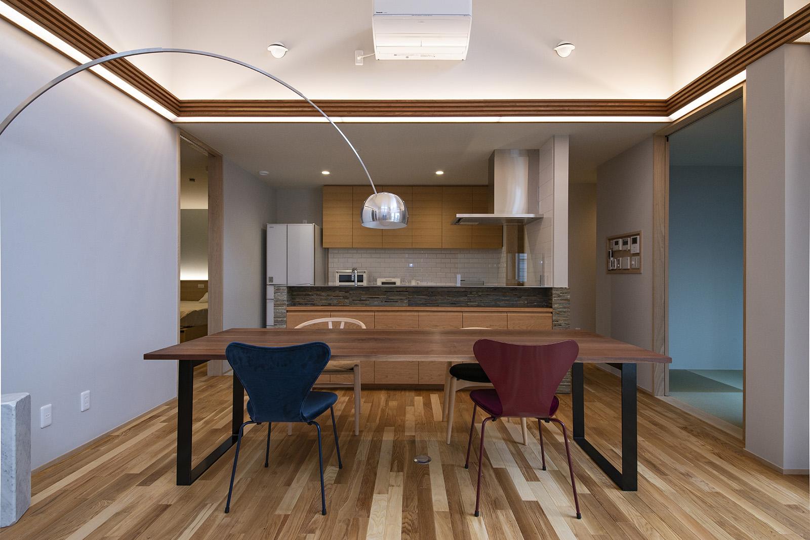 造作したダイニングテーブルとデザインが異なる椅子、フロアライトが存在感抜群