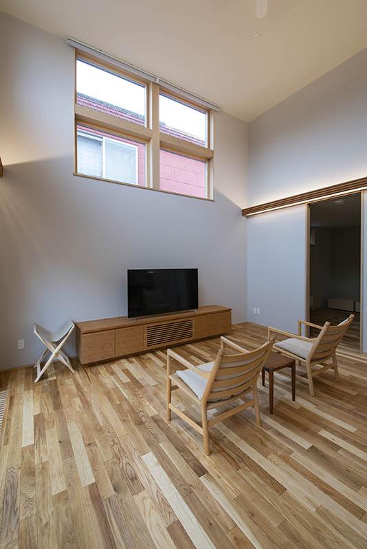 隣家が接するリビングはあえて窓を高めに設け、光を取り入れながらも目線はカバー