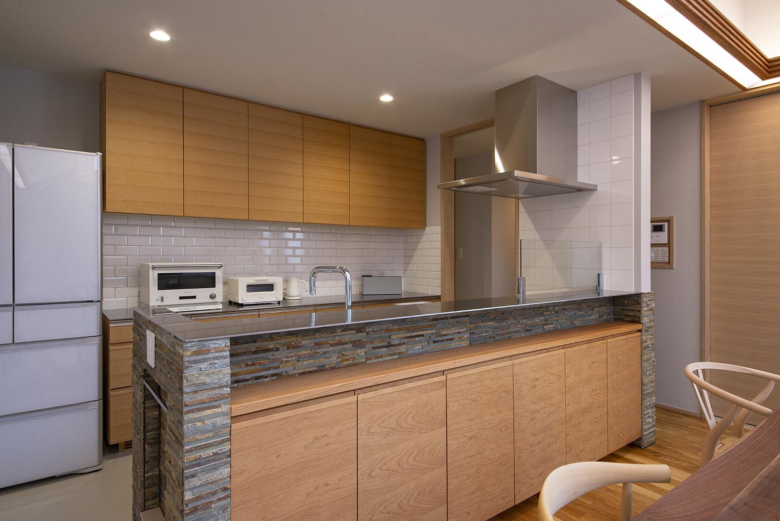 重厚な石とステンレス天板、木を組み合わせたキッチンはグレード感のある雰囲気