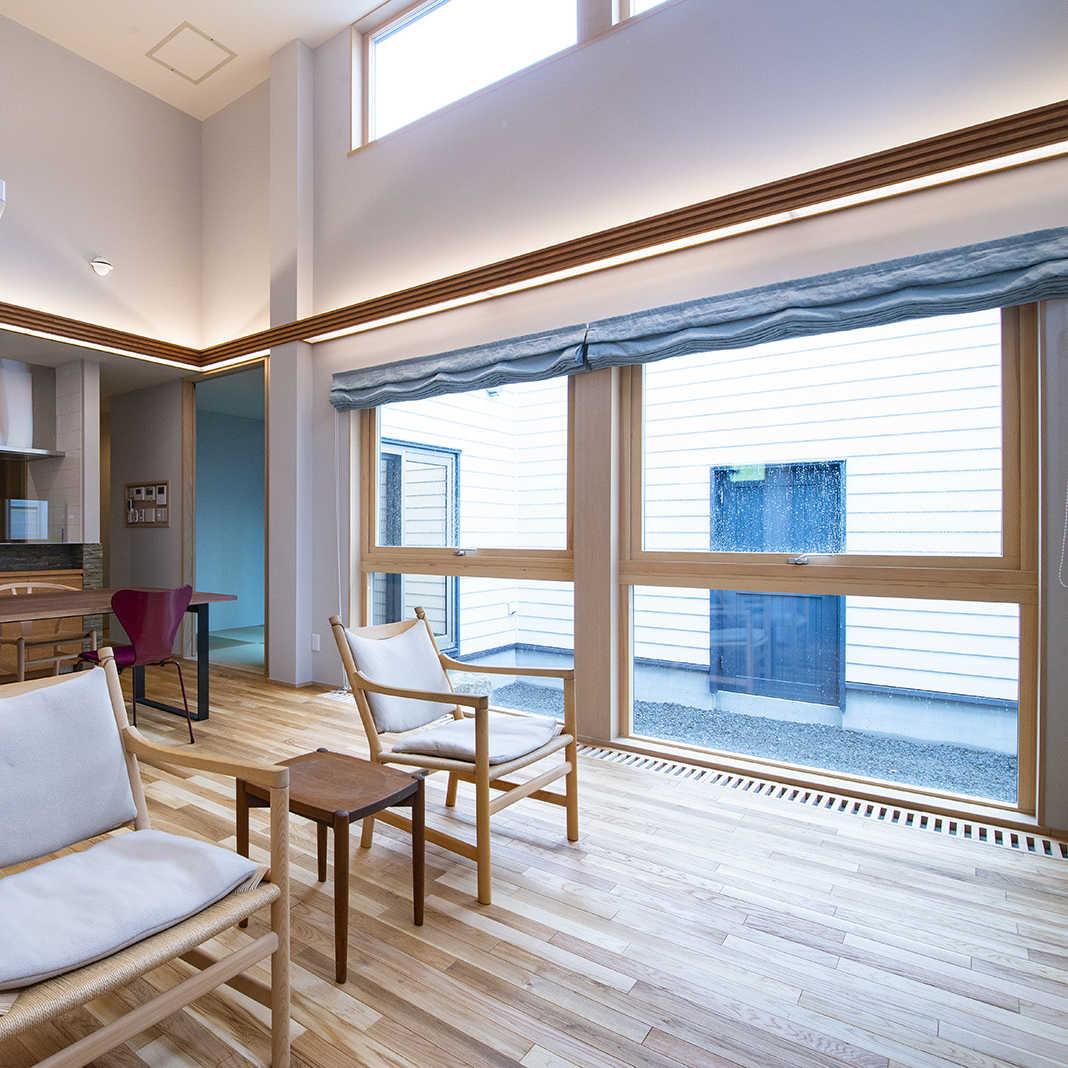 中庭を囲むようにコの字に物置と和室とリビングを配置。高い天井と窓が開放的だ