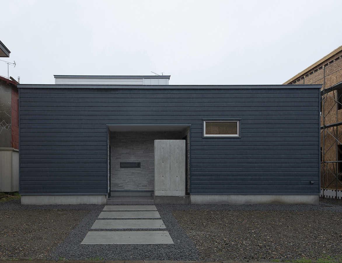 道南スギと玄関まわりの石を組み合わせ洗練されたフォルムの平屋建て