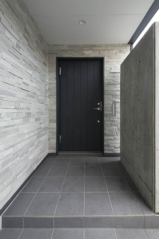 玄関のエントランスには目隠し用の壁も。石を張った壁とダークグレーの扉がスタイリッシュ
