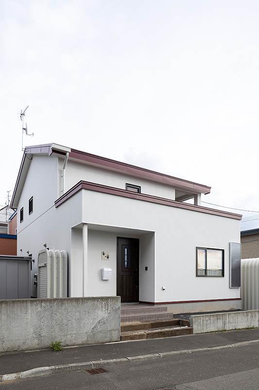 屋根の赤をアクセントにしたシンプルな白い外観。開口の脇に設置されているのが、ソーラーウォーマー