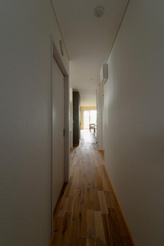 ダイニング・キッチンへ続く廊下。ダイニングに設けた掃き出し窓の光が、開口のない家の中心まで届く