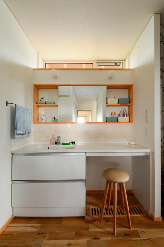 ユーティリティから独立させた洗面台は、造作棚の上に採光窓を設けて明るい雰囲気。匠工芸のマッシュルームスツールはご夫妻のお気に入り