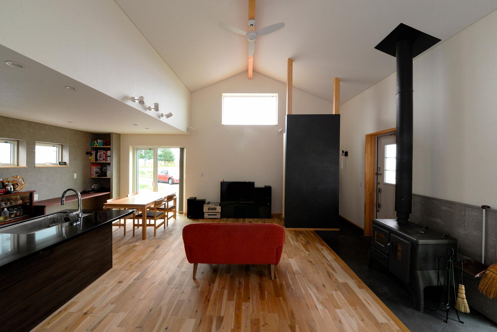 外断熱で実現した4mの天井高が心地よいLDK。黒板塗料を塗ったパーティションの向こうには、シューズクロークが設けられている