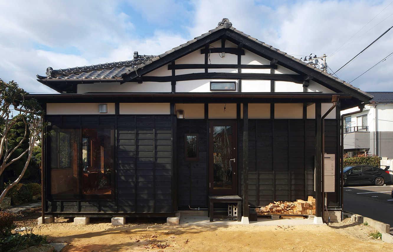 東から見るAさん宅の外観。増築部分を解体したことによって、瓦屋根に白壁と木という日本民家らしい意匠が出現。元々つながっていた部分は、板張りの外壁を新設し、既存の建物に馴染むようにしつらえた