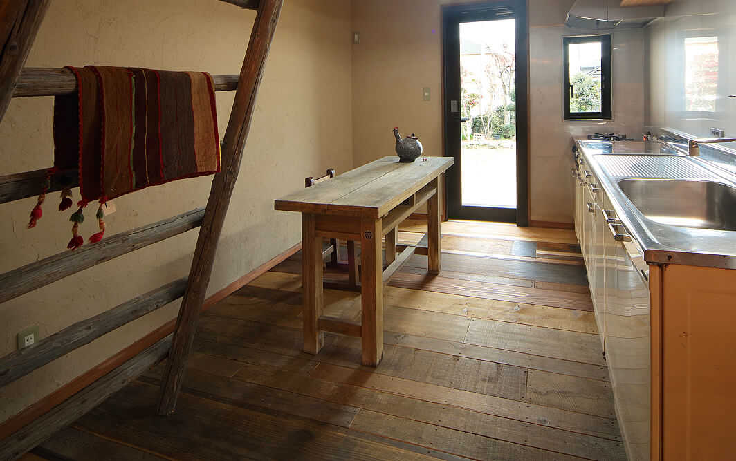 キッチンの床板は、実は幅や厚みもバラバラな古材でできている。まるで寄せ木かパッチワークのように苦労して組み合わせた甲斐あって、画一的なフローリング張りとは全く異なる表情が生まれた