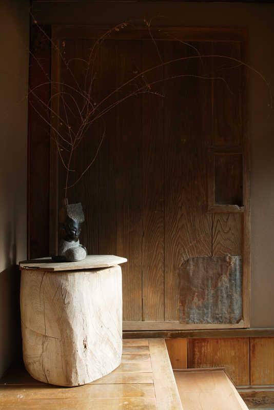 古い蔵戸と床が調和する玄関。洗い出しの床は従来の状態を活かした