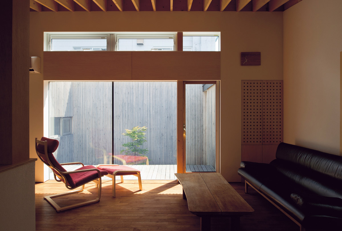 リビングには、日向ぼっこや夕涼みをしたくなる縁側のようなデッキが。リビングから床がフラットにつづいているので、空間がより広く感じられる。黒い外観とは異なり、中庭側の外壁を白くしていることも、室内が広く明るく感じられる要因