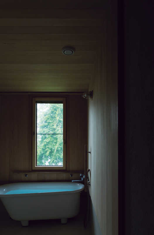 木々が繁る傾斜地に向かって開口を設けた浴室。天井と壁の仕上げにヒバ材を使用している