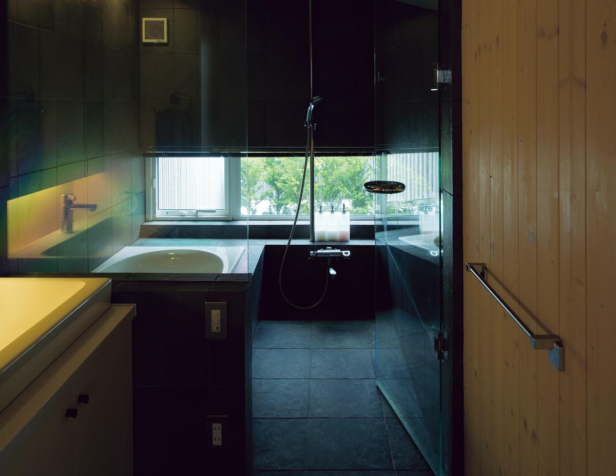 まるで露天風呂のように、風に揺らぐ木々に癒される石張りの浴室