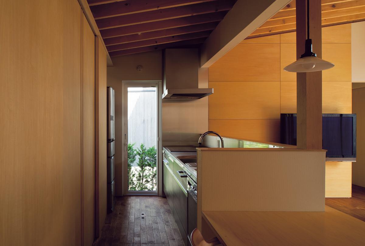 キッチンの背面は扉を設けた隠す収納でいつでもすっきり。ダイニングテーブルまで一続きなので、食事の支度もラクにできる。奥のテラスドアからは、畑のある庭に下りることができる