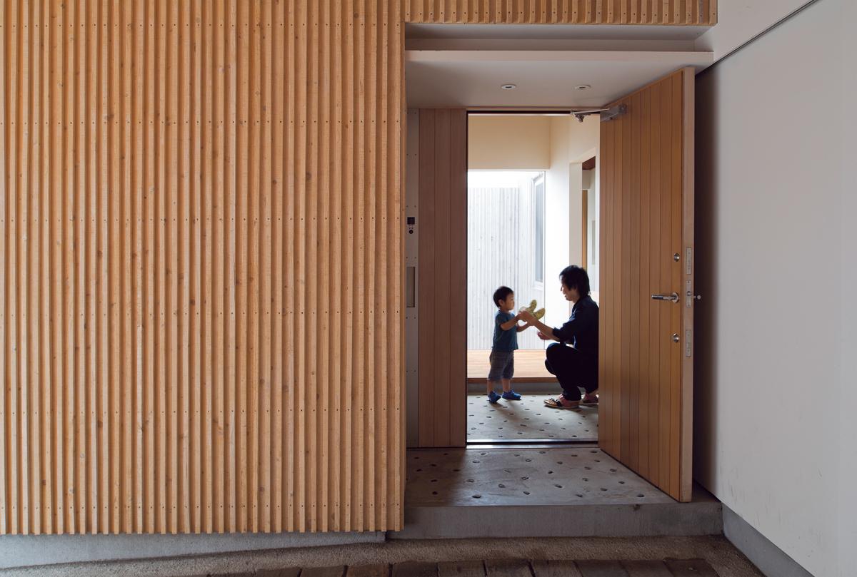 建物に組み込まれたカーポートからアプローチする玄関は、天候に左右されることなく車の乗り降りができる。玄関ドアを開けた瞬間に中庭からそそぐ光に包まれる
