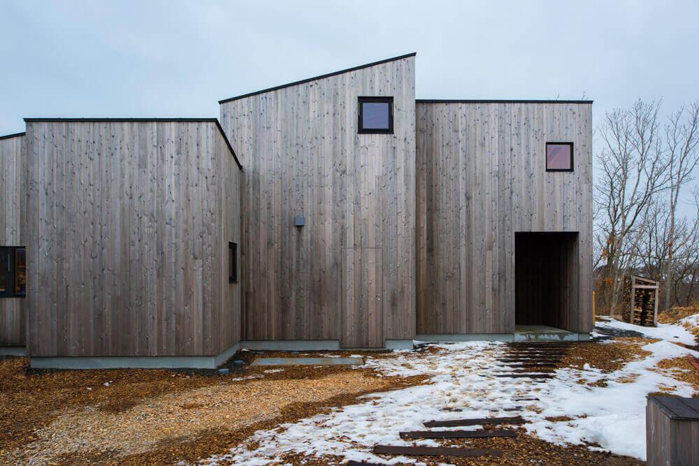 経年変化が美しい木張りの外壁にすっと空けられた玄関ポーチ