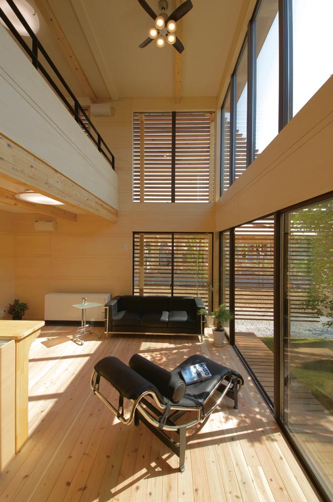 床から2階天井までの大開口に囲まれるリビング。そのまま中庭にも出られる内外のつながりが特長的