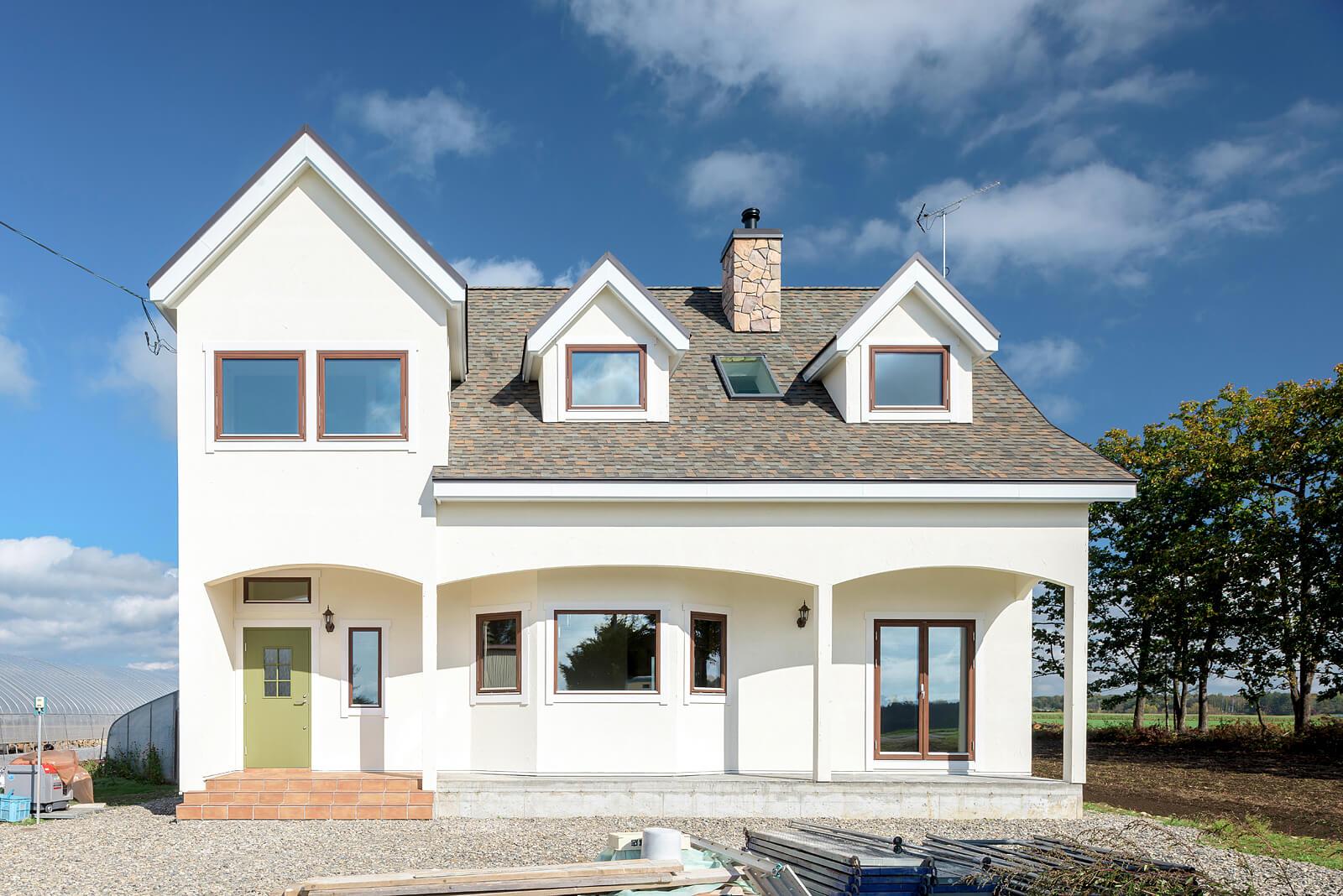 Kさん宅の外観。白い外壁に大小の三角屋根、薪ストーブの煙突が並ぶ外観は、欧州の田舎家そのもの