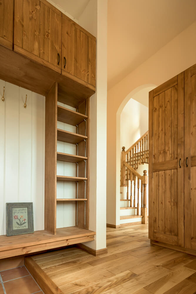 パイン材で大型収納を造作した玄関ホール。塗り壁の柔らかな白と木目がやさしいハーモニーを奏でて