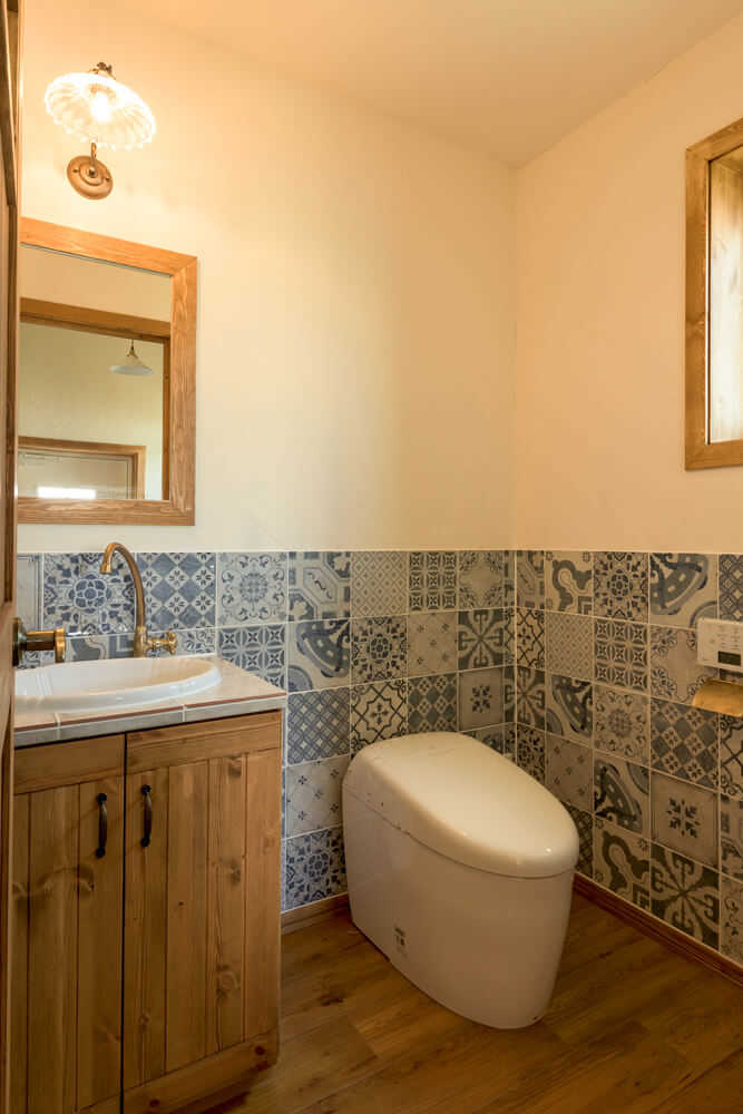 奥さんが「必ず使いたかった」という欧州のスペインタイルを採用した1階トイレ。クラシックな趣の手洗いカウンターは造作