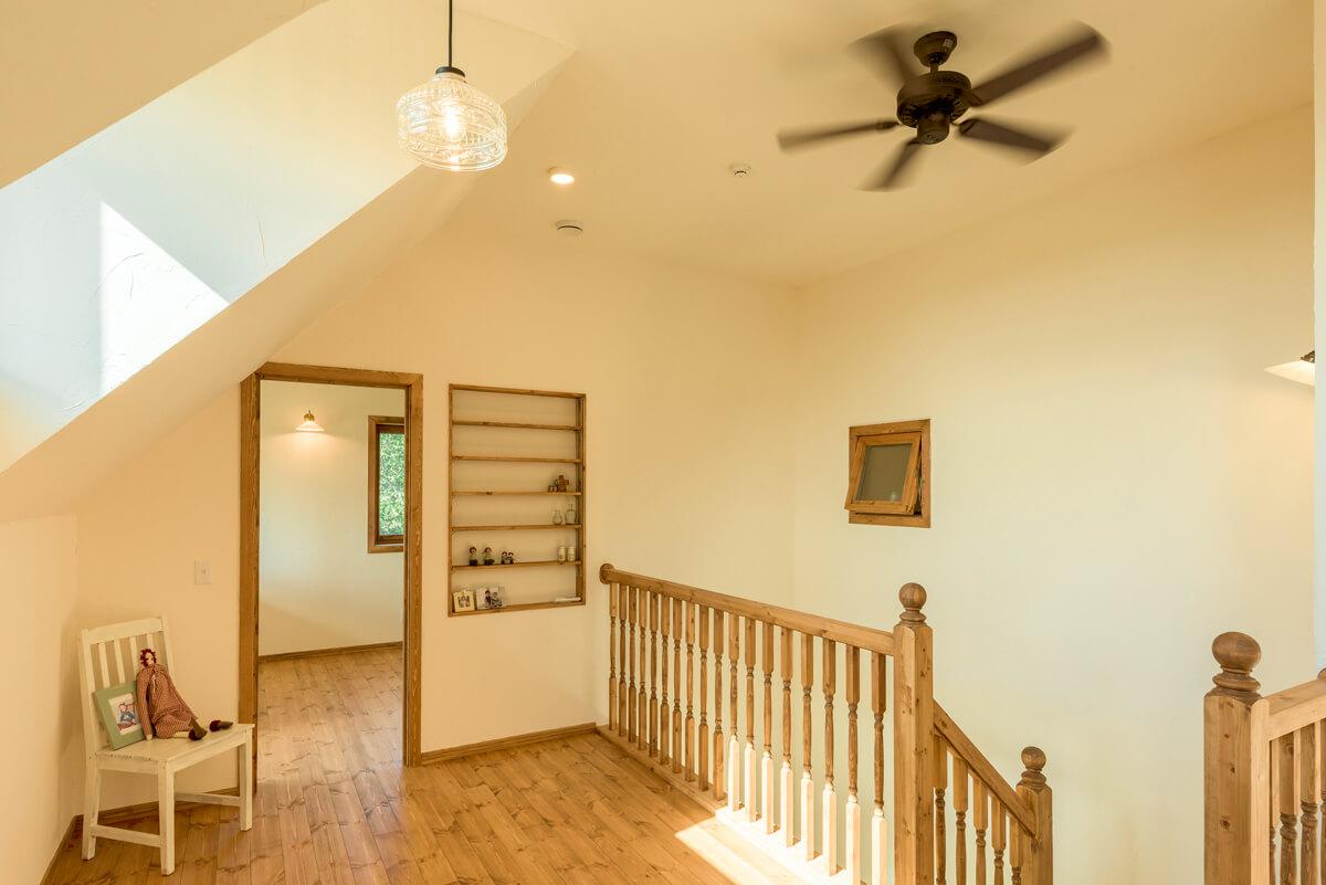 吹き抜け越しに階下のリビングを望む2階階段ホール。手すりも帯広の木工所でつくられた広岡建設のオリジナル