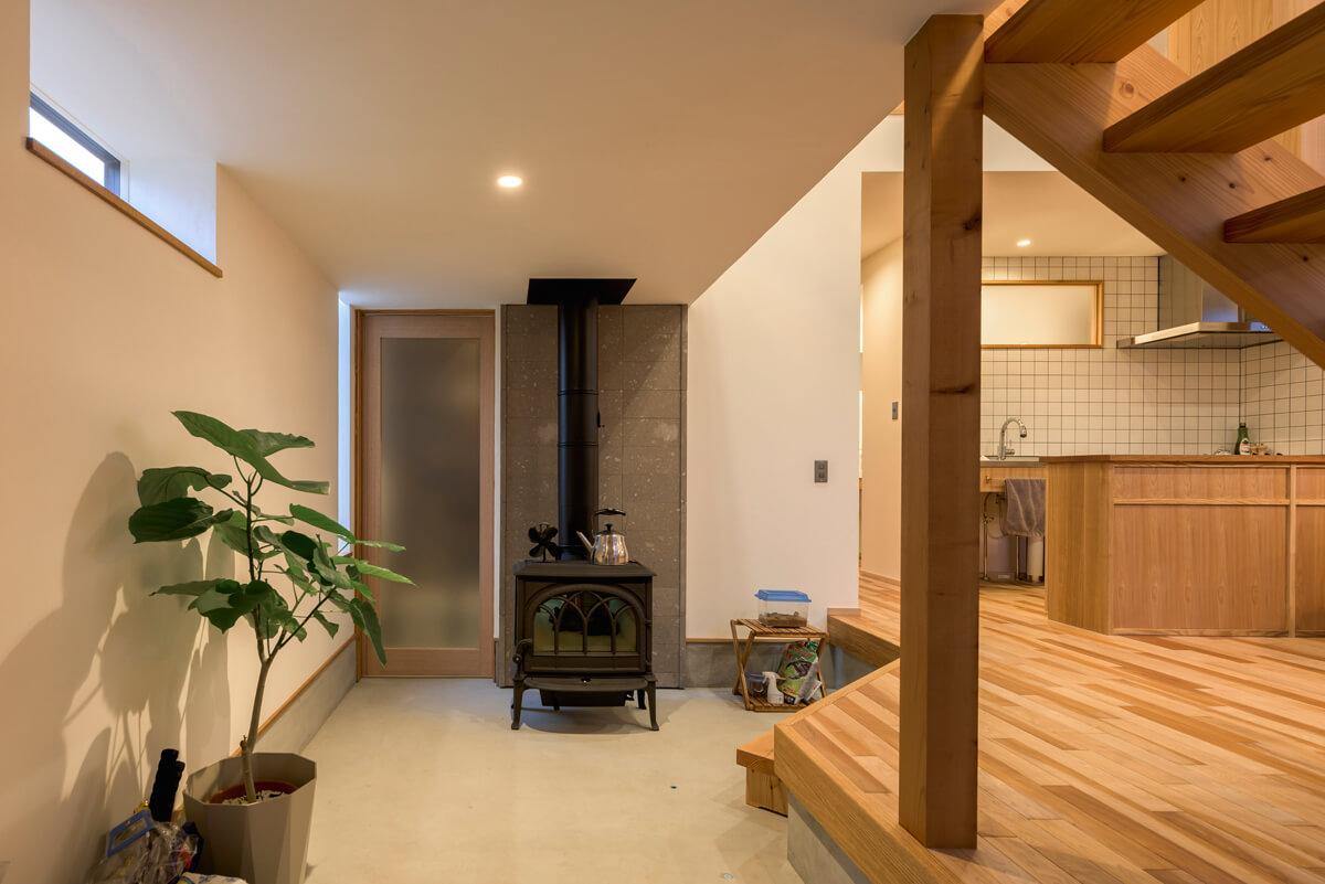 広々とした玄関土間には薪ストーブを設置。ストーブ背後の壁には札幌軟石を貼っている