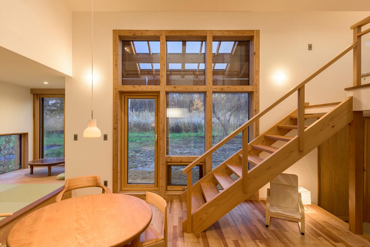 中2階と1階を繋ぐ木組みの透かし階段と木製サッシもインテリアのひとつに