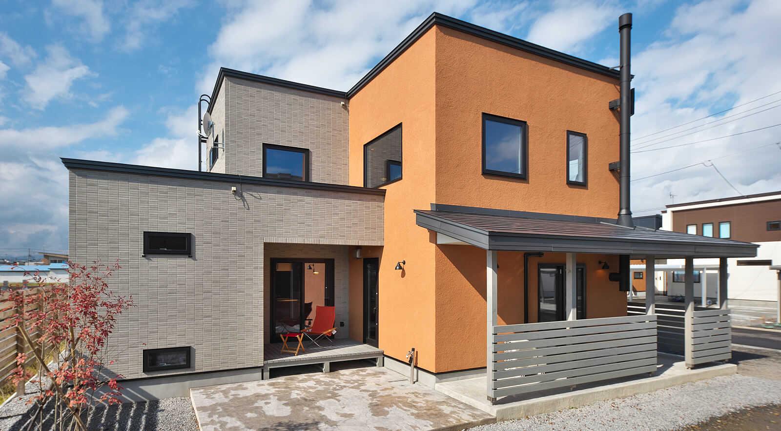 変化に富んだ横からのフォルム。意匠性とメンテナンスに優れた塗り壁仕上げに、オレンジ色が個性を際立たせる