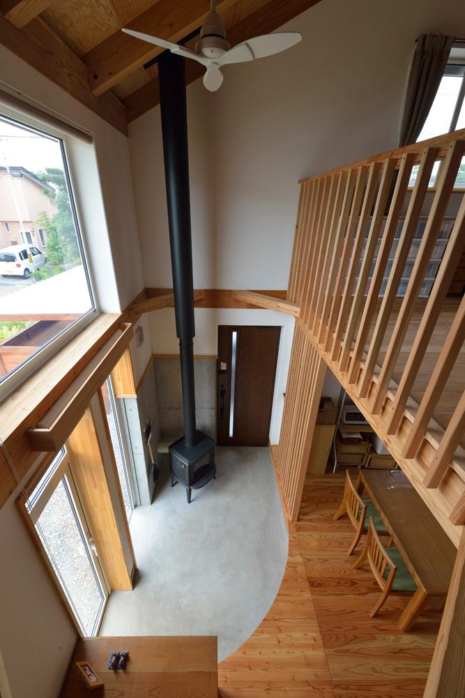 新在来工法により実現した高い住宅性能が、玄関土間に設置した薪ストーブ1台での全館暖房を可能に。大らかな吹き抜けが、階下の家族の気配と共にストーブの熱も2階へと運ぶ