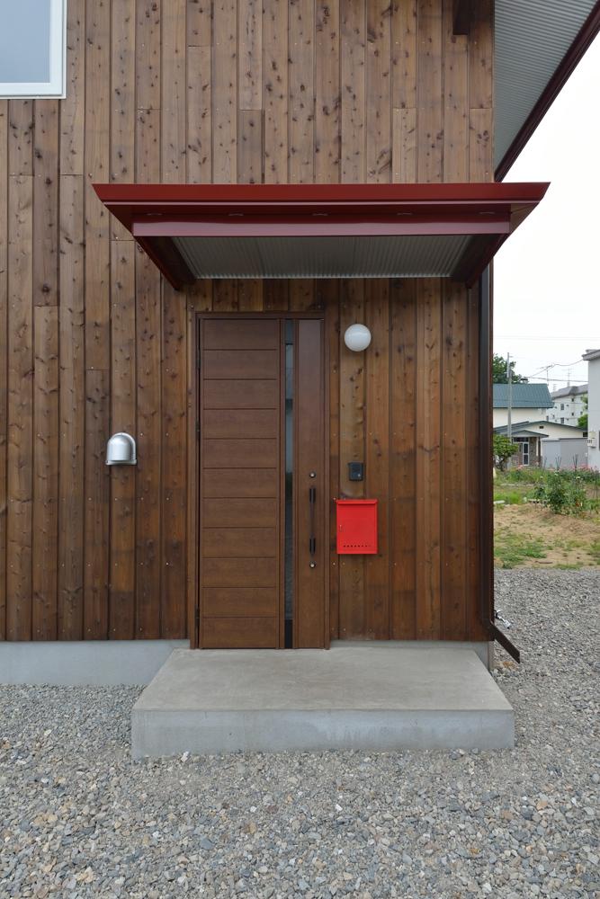 玄関にも、カラマツの外壁に馴染む断熱ドアを採用。軒裏にはガルバリウム鋼板を張り、さりげないアクセントに