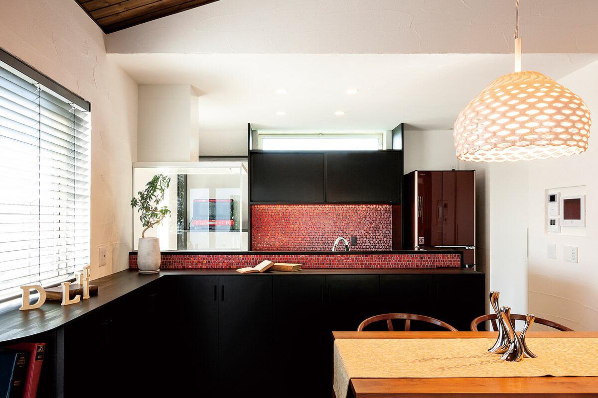 黒い造作キッチンにビビッドな赤いモザイクタイルが、シックでありつつ強いインパクトを感じさせる