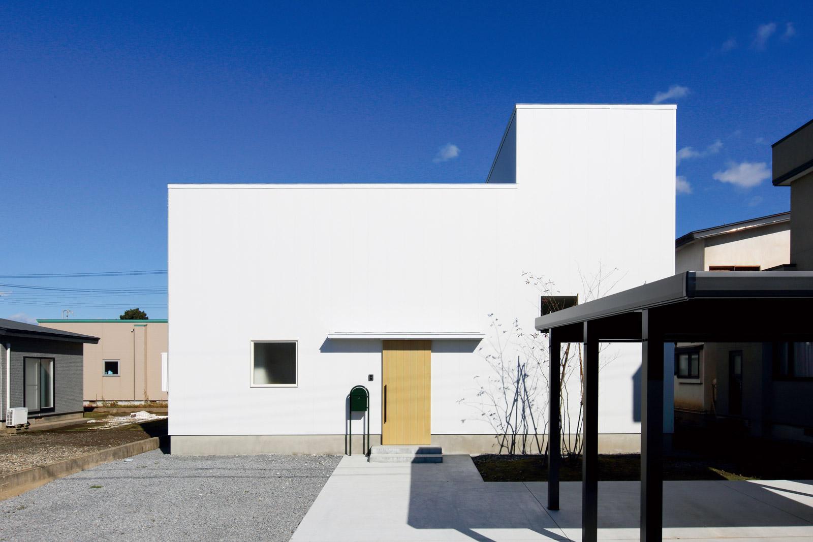南側外観。4棟の隣家に囲まれており、それぞれの住宅の高さに合わせて視線を制御している