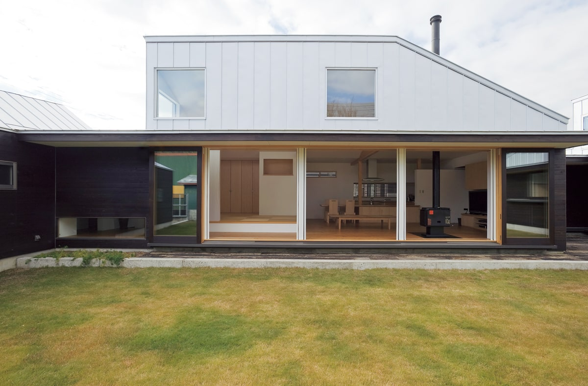 リビングと中庭をつなぐ大きな窓は木製の造作。開け放した時には外壁部分に重なり、開口を広く確保できる