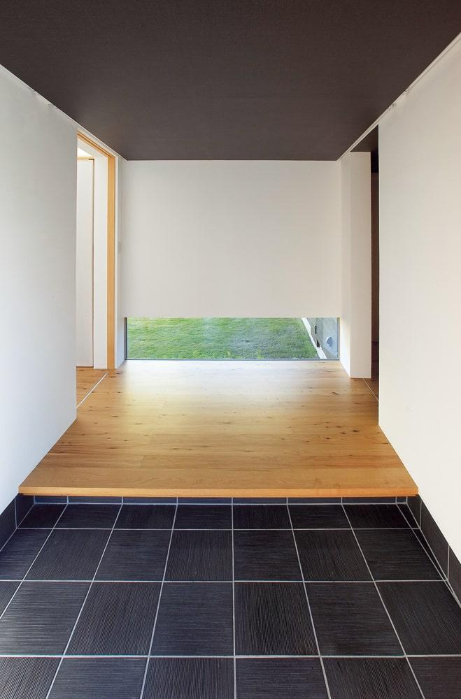 玄関に入るとシンプルな空間と地窓。窓の外に広がる中庭の雰囲気が伝わってくる