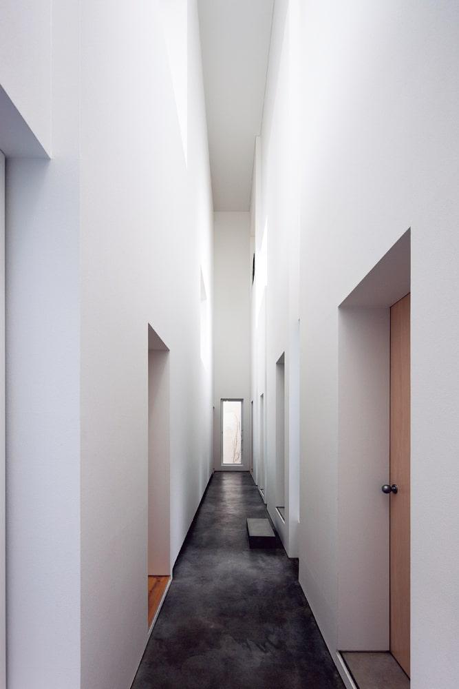 玄関を入り、リビング・ダイニングへと向かう。上からの光、壁に反射する光が心地よく広がる