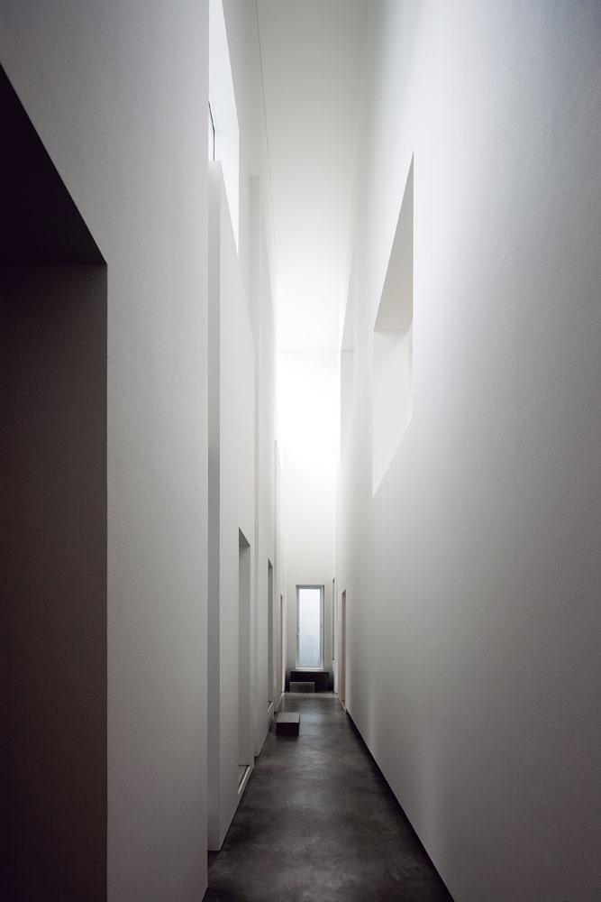 家の中心を貫くホールは天井高8m。 上部は各居室とつながる窓が開けられている