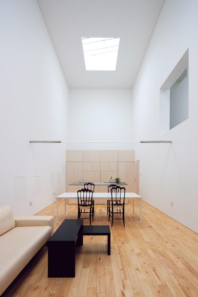 リビング・ダイニング。窓のない壁に圧迫感ではなく包まれるような安心感を感じるのは、この高さと光のグラデーションが成す効果