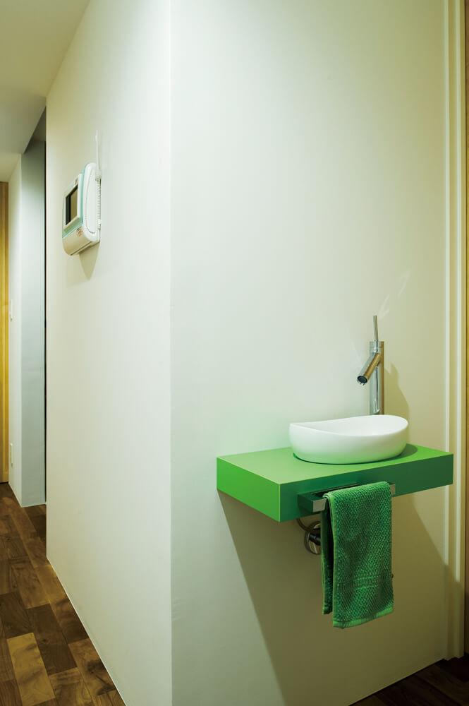 2階トイレ前の手洗器の台座も鮮やかなグリーンで、空間が華やぐ