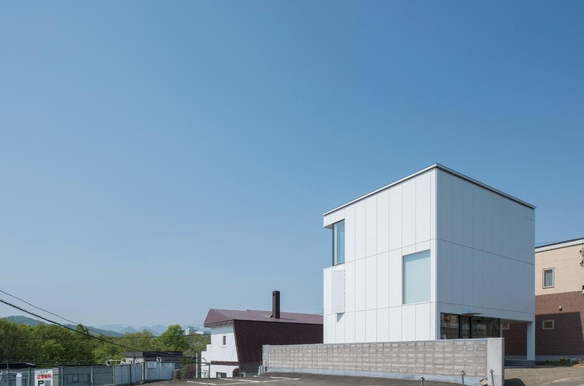 あらかじめパネル状に加工した白いガルバリウム鋼板を張った外壁