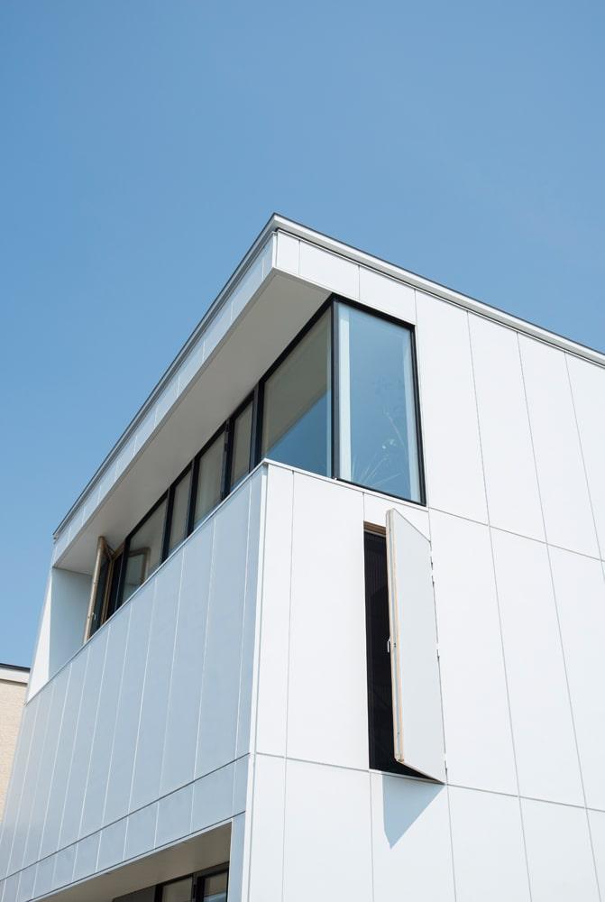 外壁に開いたスリットは対角にも設けられ、通風口の役割を果たす。3階の大開口はセットバックし、外部からの視線を遮断