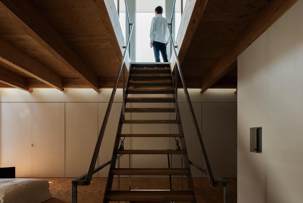 明暗のコントラストが印象的な2つのフロアを結ぶ階段。3階窓際のスリットからこぼれる光が2階の壁をやさしく照らして