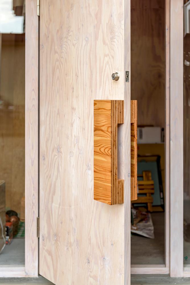 風除室のドアの塗装や木目を生かした取っ手も佐藤さんが手掛けたもの。塗装は水野建設の平さんも手伝った