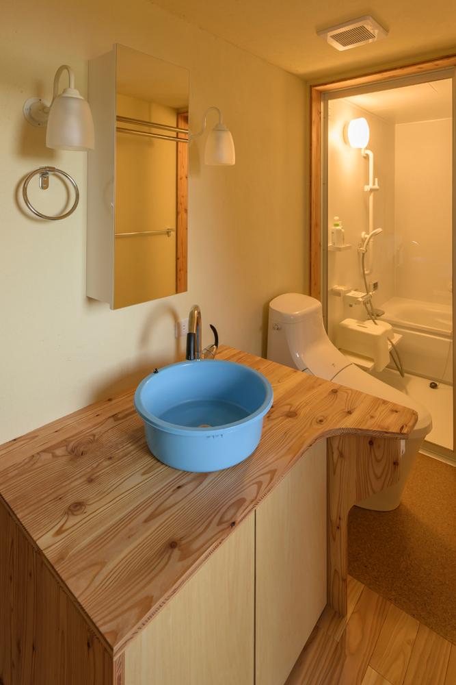 水まわりとトイレは1ヵ所に集約し、浴室にはガラスの間仕切りを採用。造作洗面台には後日、陶器製のボウルを設置する予定