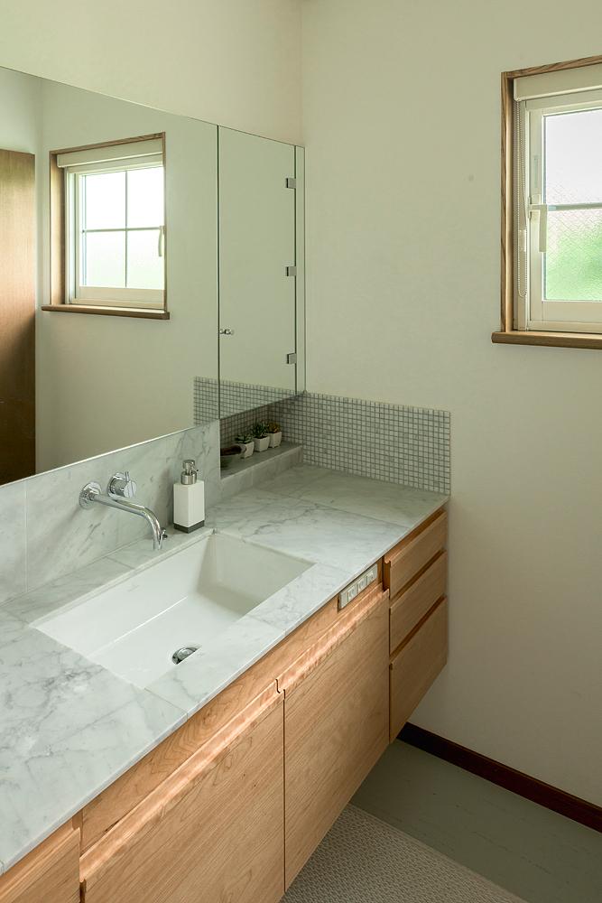 洗面台もキッチンと素材を合わせた造作仕様。美しく広々とした空間は、奥さん一番のお気に入りだそう