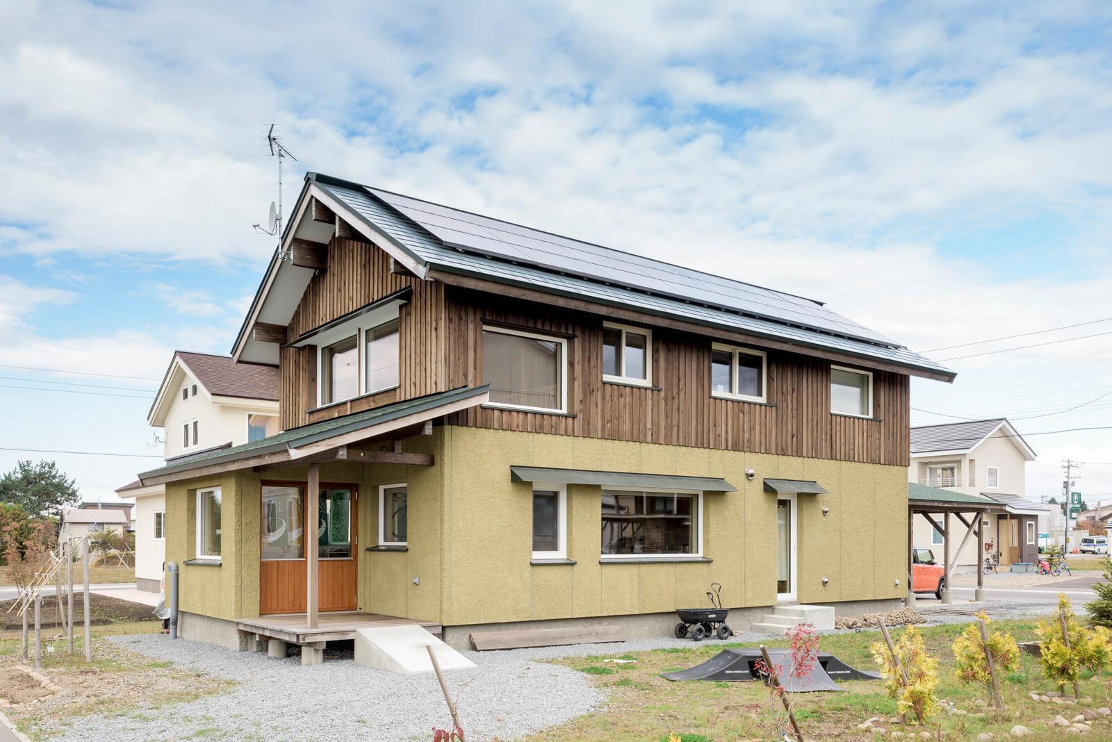 メンテナンスフリーのウッドトリートメントを塗布したカラマツ材と、いつまでも色落ちしない色粉を練り込んだはきつけモルタル外壁の外観が、周囲の風景に馴染んでいる。南東面の屋根には太陽光発電パネルを搭載した