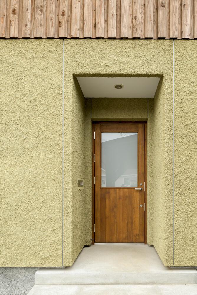 木の質感が心地よい玄関の木製ドア。モルタルとの相性も良い