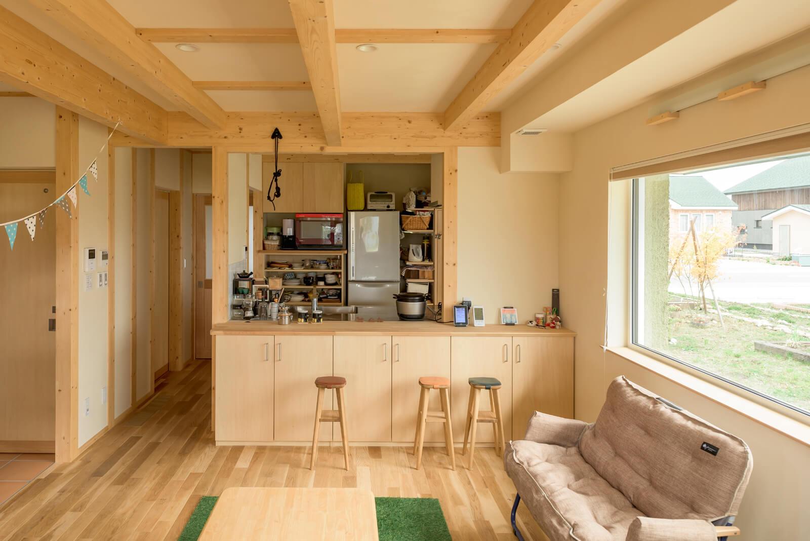 キッチン前のカウンターには、色違いのスツールが3つ並ぶ。カウンター下には家族それぞれの棚が設けられている